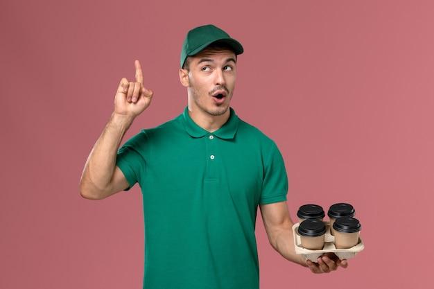 Vue de face jeune homme en uniforme vert tenant des tasses de café marron sur fond rose