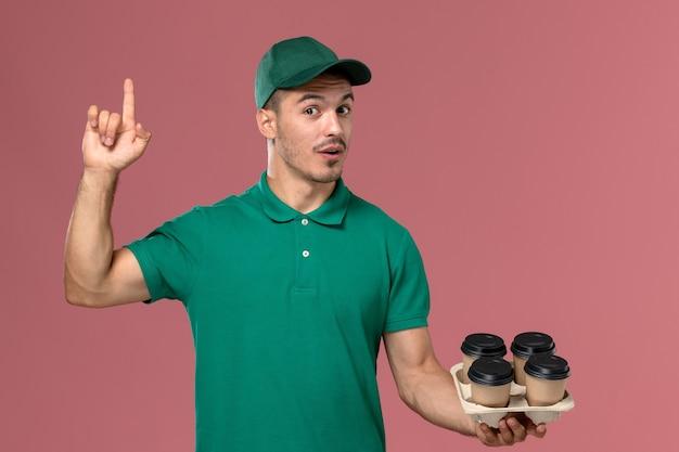 Vue de face jeune homme en uniforme vert tenant des tasses de café marron levant son doigt sur le sol rose clair