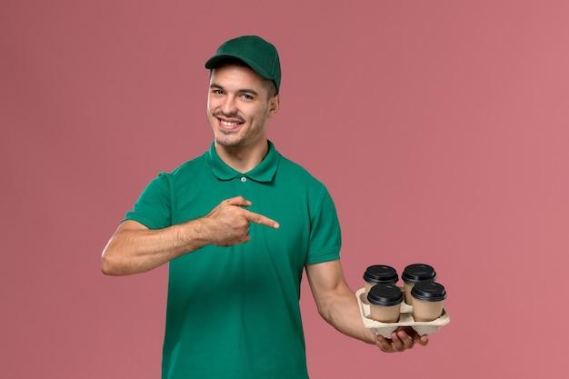 Vue de face jeune homme en uniforme vert tenant des tasses à café marron avec un sourire sur un bureau rose