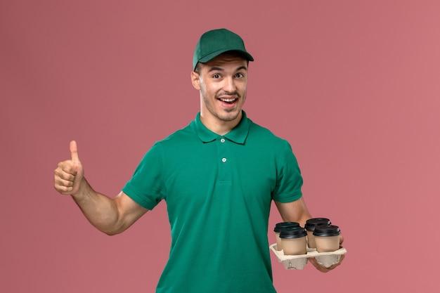 Vue de face jeune homme en uniforme vert tenant des tasses de café se réjouissant sur fond rose