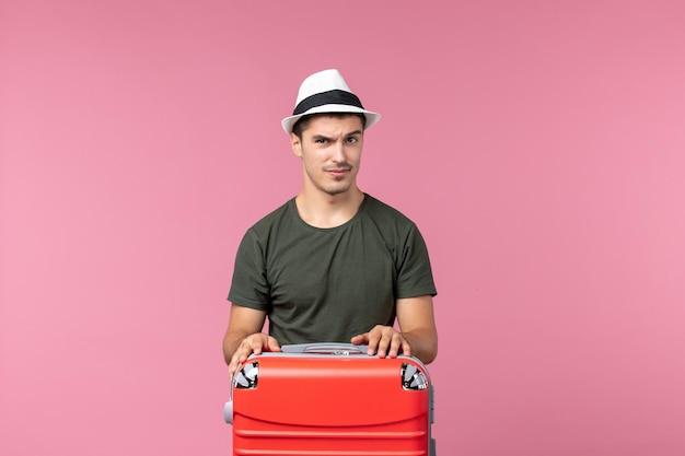 Vue de face jeune homme en vacances sur un espace rose clair