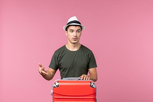 Vue de face jeune homme en vacances avec grand sac sur espace rose