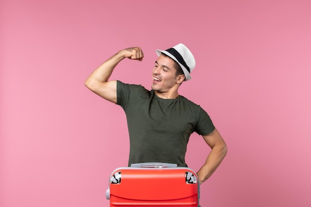 Vue de face jeune homme en vacances montrant sa force sur un espace rose