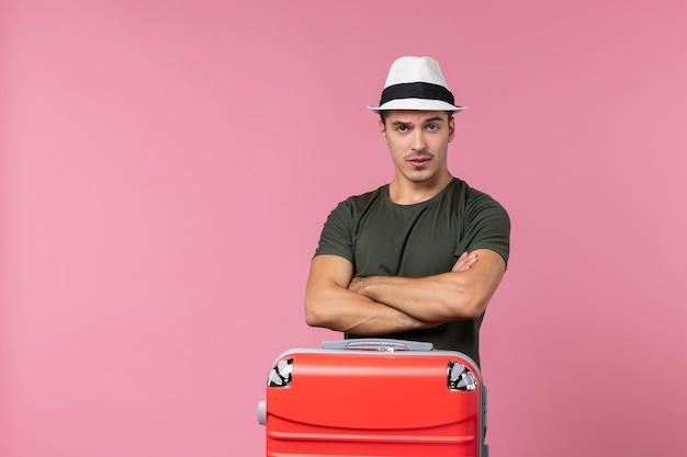 Vue de face jeune homme en vacances portant un chapeau sur un espace rose clair