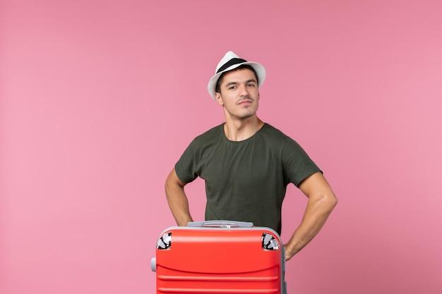 Vue de face jeune homme en vacances portant un chapeau sur l'espace rose