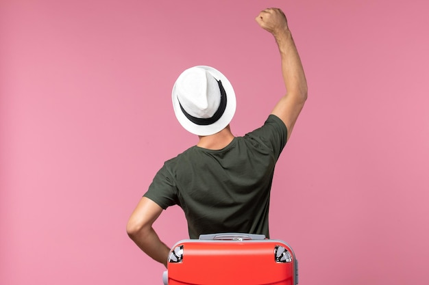 Vue de face jeune homme en vacances portant un chapeau sur le sol rose voyage homme voyage en mer vacances voyage