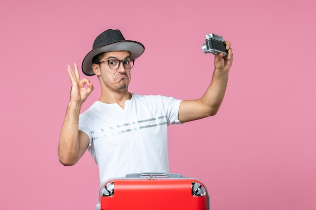 Vue de face d'un jeune homme en vacances avec un sac tenant un appareil photo prenant des photos sur un mur rose clair