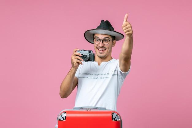 Vue de face d'un jeune homme en vacances avec un sac tenant un appareil photo prenant des photos sur le mur rose