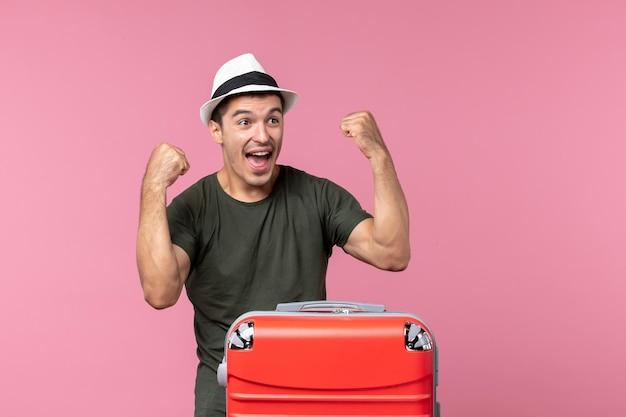 Vue de face jeune homme en vacances se réjouissant de l'espace rose