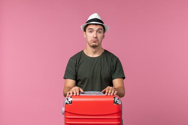 Vue de face jeune homme en vacances avec son sac rouge sur un bureau rose