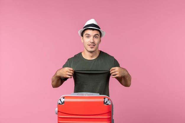 Vue de face jeune homme en vacances avec son sac rouge sur un espace rose clair