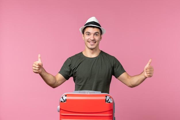 Vue de face jeune homme en vacances avec son sac rouge souriant sur un espace rose