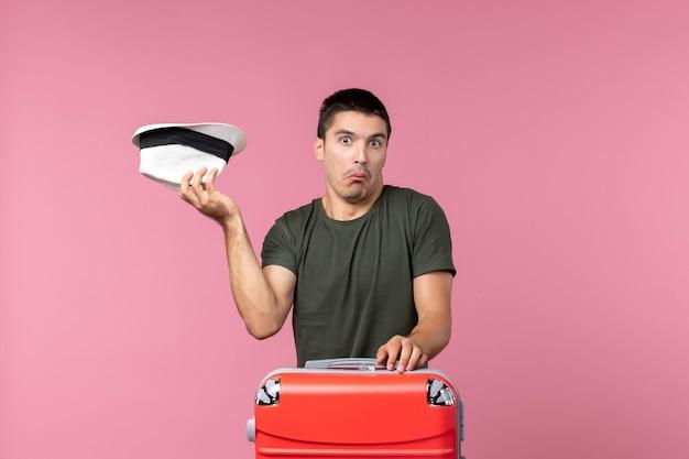 Vue de face jeune homme en vacances tenant son chapeau sur un espace rose clair
