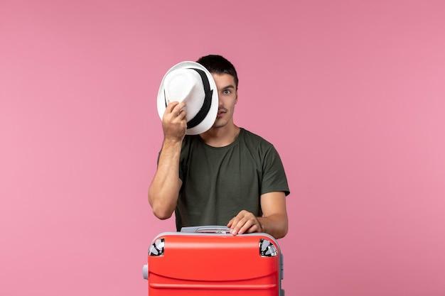 Vue de face jeune homme en vacances tenant son chapeau sur l'espace rose