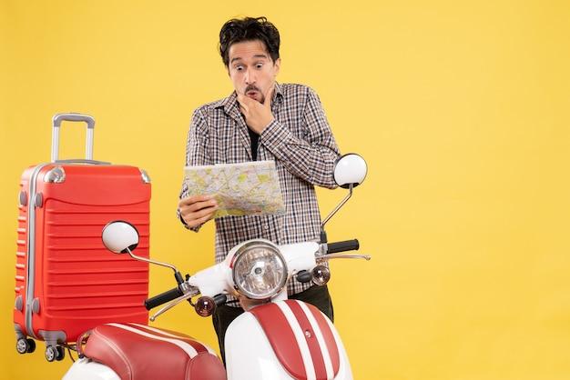 Vue de face jeune homme avec vélo observation de la carte avec une expression surprise sur jaune