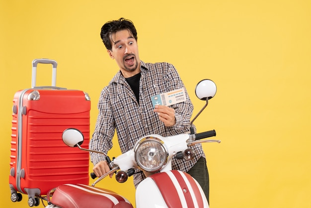 Vue de face jeune homme avec vélo et sac tenant un billet sur jaune