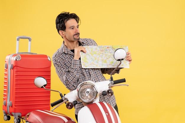 Vue de face jeune homme avec vélo tenant la carte sur jaune