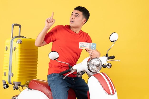 Vue de face jeune homme en vêtements décontractés sur un billet d'avion tenant un cyclomoteur