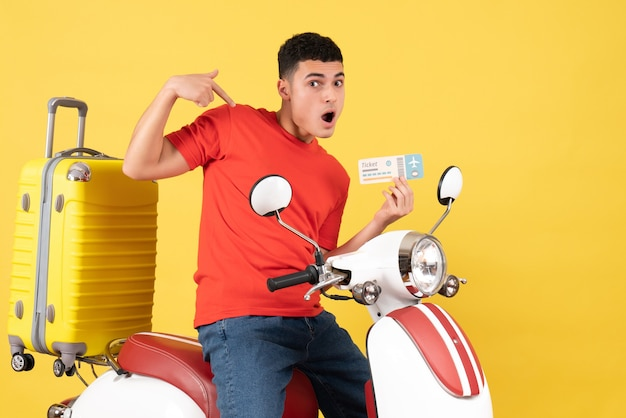Vue de face jeune homme en vêtements décontractés sur un billet de maintien cyclomoteur pointant sur lui-même