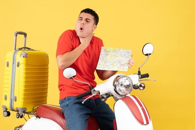 Vue de face jeune homme en vêtements décontractés sur cyclomoteur avec carte de voyage tenant la gorge avec douleur
