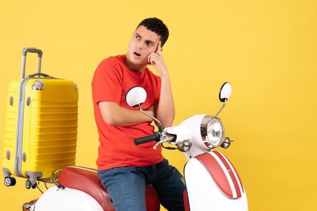 Vue de face jeune homme en vêtements décontractés sur un cyclomoteur pensant à quelque chose