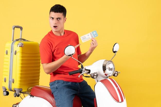 Vue de face jeune homme en vêtements décontractés sur un cyclomoteur pointant sur un billet d'avion