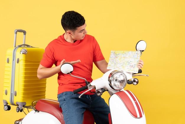 Vue de face jeune homme en vêtements décontractés sur cyclomoteur en regardant la carte de voyage
