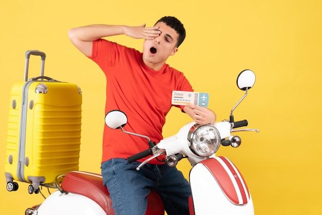 Vue de face jeune homme en vêtements décontractés sur un cyclomoteur tenant un billet de voyage
