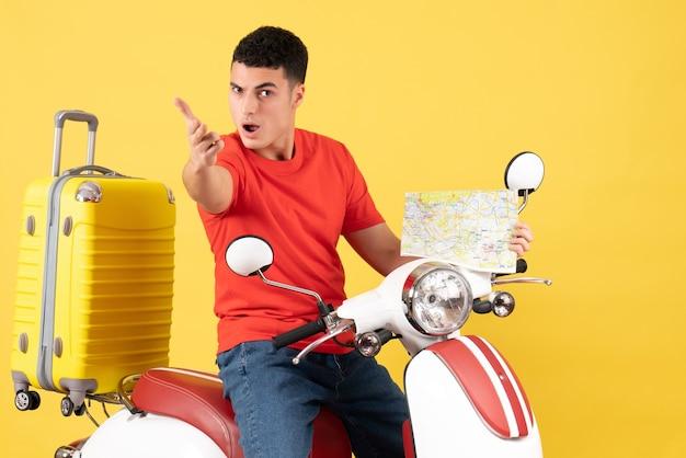 Vue de face jeune homme en vêtements décontractés sur cyclomoteur tenant une carte de voyage atteindre la main