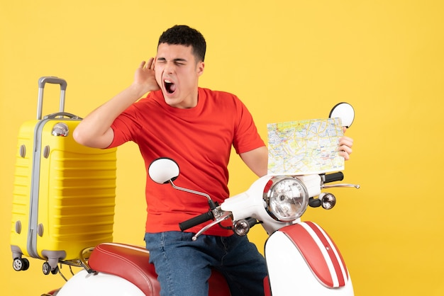 Vue de face jeune homme en vêtements décontractés sur un cyclomoteur tenant une carte de voyage en écoutant quelque chose