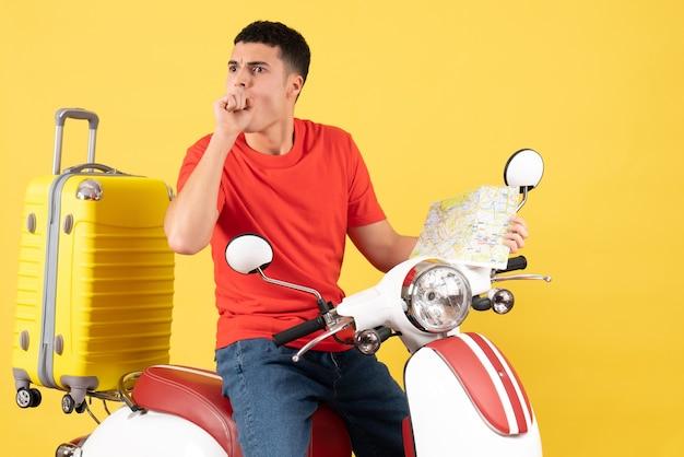 Vue de face jeune homme en vêtements décontractés sur cyclomoteur tenant une carte de voyage en regardant quelque chose
