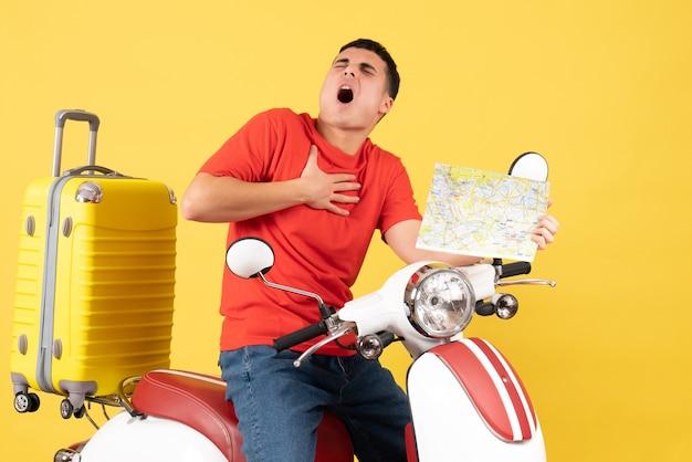 Vue de face jeune homme en vêtements décontractés sur cyclomoteur tenant coeur avec douleur