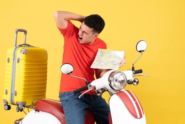 Vue de face jeune homme en vêtements décontractés sur cyclomoteur tenant sa tête avec douleur