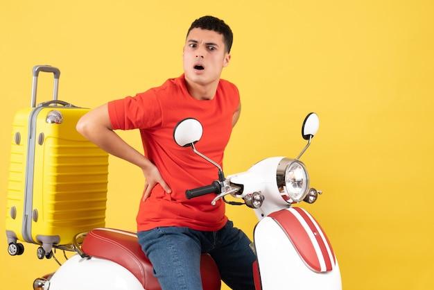 Vue de face jeune homme en vêtements décontractés sur cyclomoteur avec valise mettant la main sur une taille
