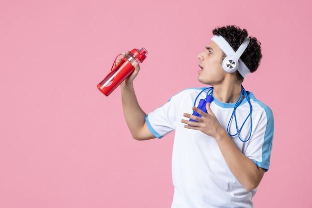 Vue de face jeune homme en vêtements de sport avec une bouteille d'eau et des cordes à sauter sur le mur rose