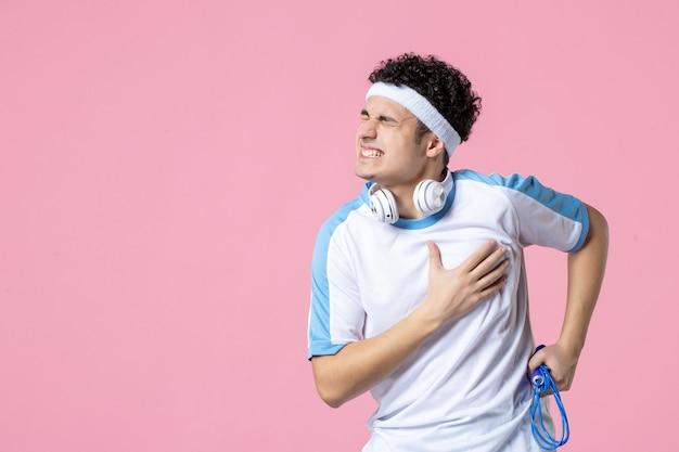 Vue de face jeune homme en vêtements de sport avec corde à sauter ayant le chagrin sur le mur rose
