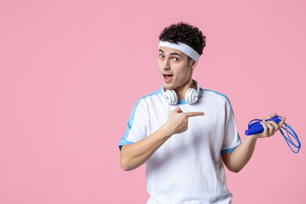 Vue de face jeune homme en vêtements de sport avec corde à sauter sur le mur rose