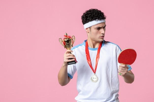 Vue de face jeune homme en vêtements de sport avec médaille et coupe d'or sur mur rose