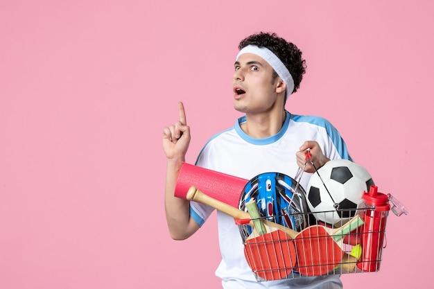 Vue de face jeune homme en vêtements de sport avec panier plein de choses de sport mur rose