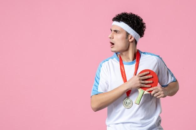 Vue de face jeune homme en vêtements de sport avec raquette et médaille sur mur rose