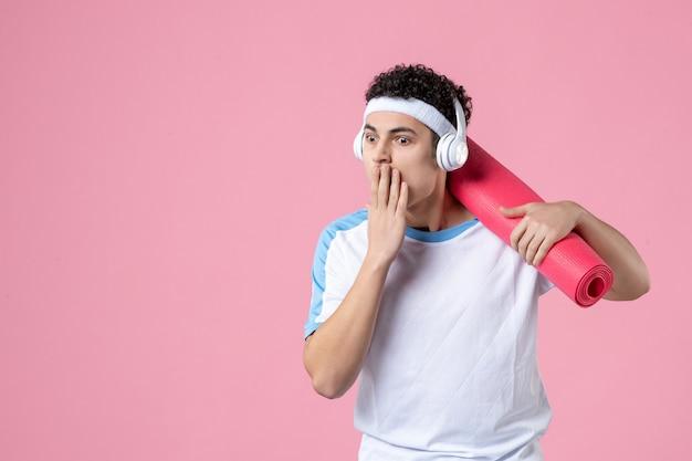Vue de face jeune homme en vêtements de sport avec tapis de yoga et écouteurs sur mur rose