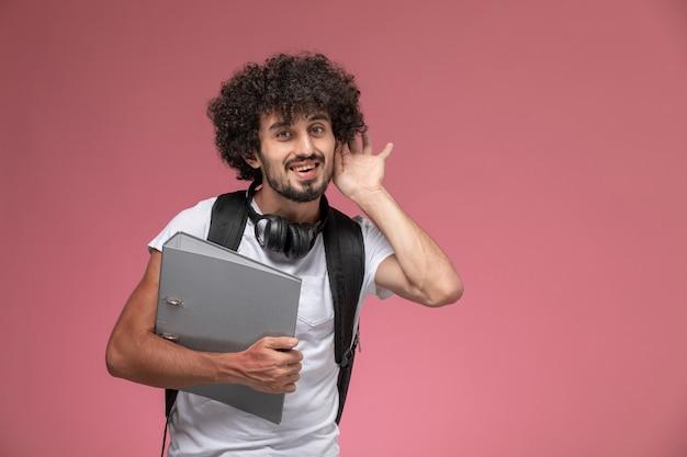 Vue de face jeune homme veut entendre avec classeur