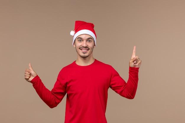 Vue de face jeune homme avec visage excité sur fond marron vacances d'émotion de noël mâle