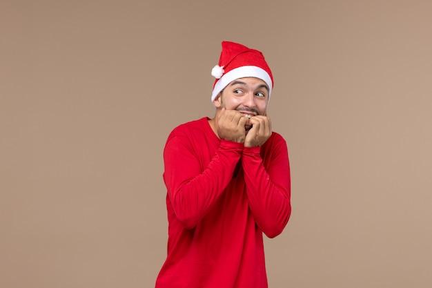 Vue de face jeune homme avec visage excité sur fond marron vacances émotions masculines