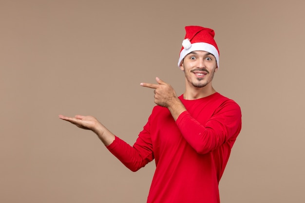 Vue de face jeune homme avec visage excité sur plancher brun vacances d'émotion de noël