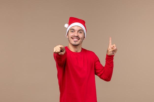 Vue de face jeune homme avec visage souriant sur fond marron vacances de noël émotions mâle