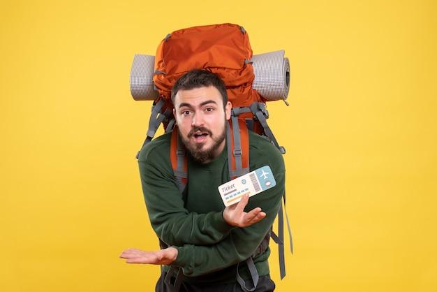 Vue de face d'un jeune homme de voyage confus avec sac à dos et montrant un billet sur fond jaune