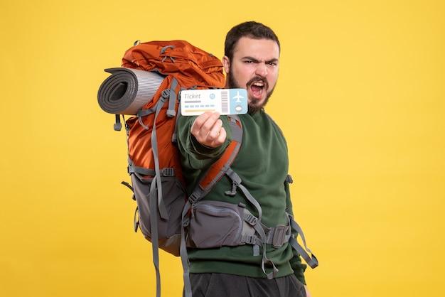 Vue de face d'un jeune homme de voyage émotionnel avec sac à dos et montrant un billet sur fond jaune