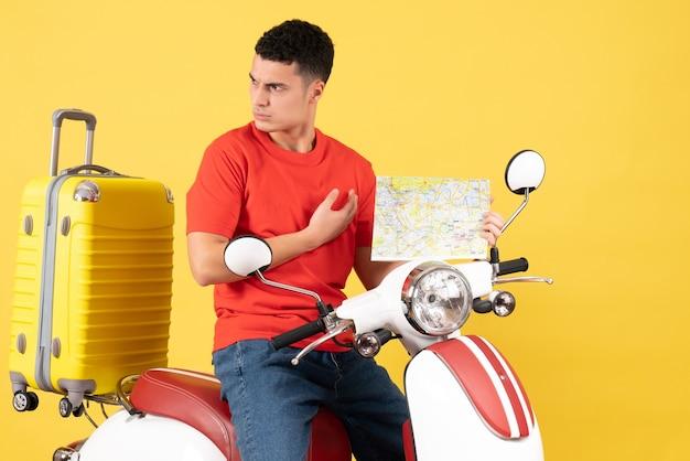 Vue de face jeune homme voyageur en vêtements décontractés sur cyclomoteur tenant une carte de voyage