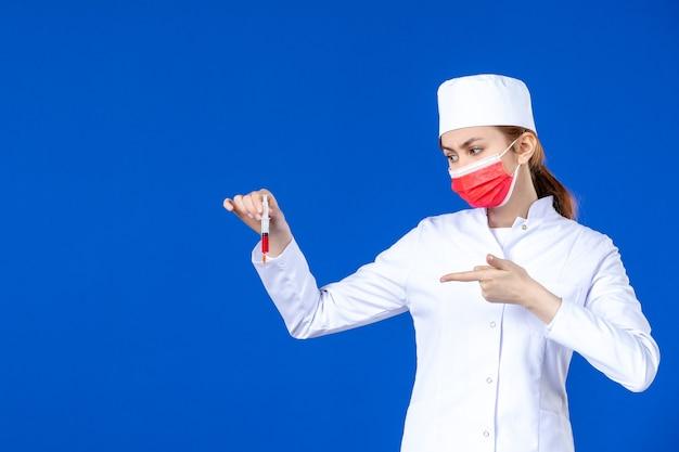 Vue de face jeune infirmière en costume médical blanc avec masque rouge et injection dans ses mains sur le mur bleu